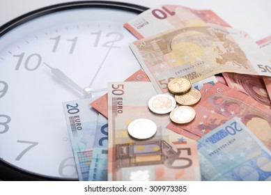 Euro banknotes on a clock