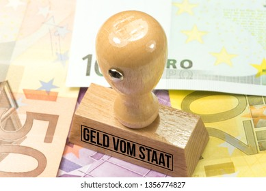 Euro banknotes, stamp and German translation for money from the state