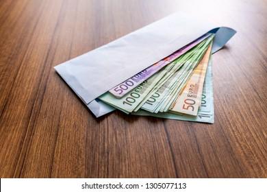 Euro banknotes in white envelope. Open envelope with money banknotes on table. White envelope with Euro money  bills. Closeup on Envelope full of euro cash. International currency monetary