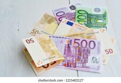 Euro bills of 500, 100 and 50 banknotes over wooden table