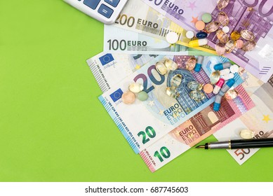 Euro bills with different pills and pen on green