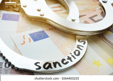 Euro bills and handcuffs with word sanctions. Economical restrictive measures.