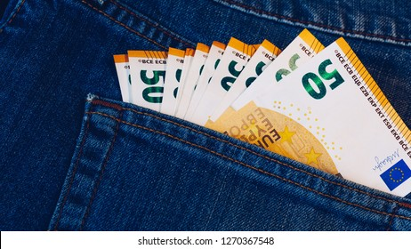 Euro bills in jeans pocket background. Euro banknotes in jeans back pocket. Concept of rich people, saving or spending money. Euro bills falling out. Easy to steal the money. Irresponsible action.