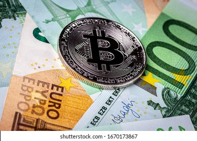 Euro bills and metal souvenir bitcoin. The concept of electronic money and commerce. Cryptocurrency and cash.