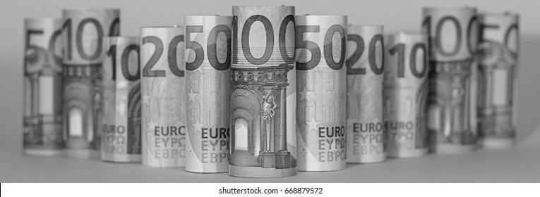 Euro bills rolled up and stand in a row, Several different euro banknotes stacked by value, Euro currency money, in black and white, panorama
