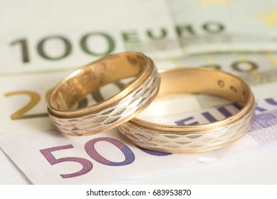 Euro bills and two wedding rings