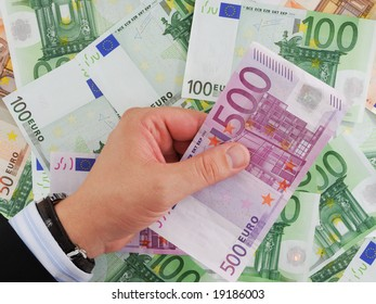 Euro in businessman hand on background with money.