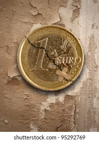 euro coin with crack and sticking plaster