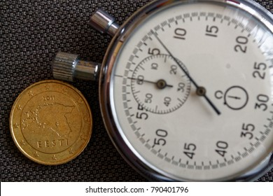 Euro coin with a denomination of 50 euro cents (back side) and stopwatch on brown denim backdrop - business background