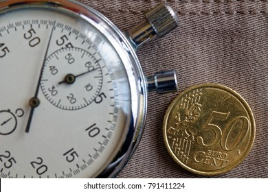 Euro coin with a denomination of fifity euro cents and stopwatch on worn beige denim backdrop - business background