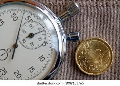Euro coin with a denomination of twenty euro cents and stopwatch on worn beige denim backdrop - business background