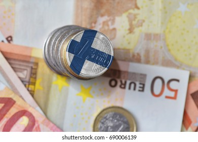 euro coin with national flag of finland on the euro money banknotes background. finance concept