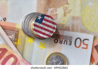 euro coin with national flag of liberia on the euro money banknotes background. finance concept
