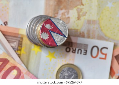 euro coin with national flag of nepal on the euro money banknotes background. finance concept