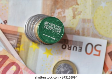 euro coin with national flag of saudi arabia on the euro money banknotes background. finance concept