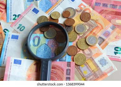 Euro coins, cents, notes and magnifying glass