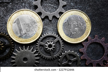 Euro coins and gears on dark background