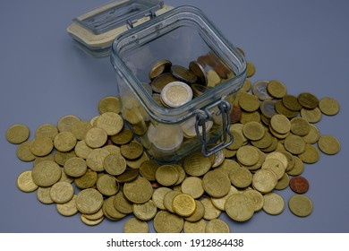 Euro coins, one of which is Italian, in an airtight glass jar, with the lid open, with other money next to it. Public debt concept