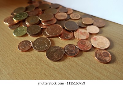Euro coins of small value left on bookshelf (focus in foreground).