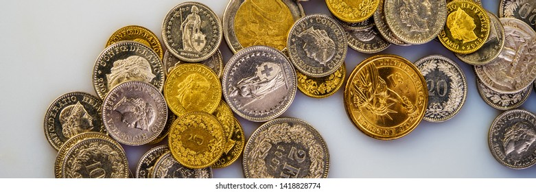 Euro coins, Swiss francs, the American dollar lie on a light background. Web banner for your design.