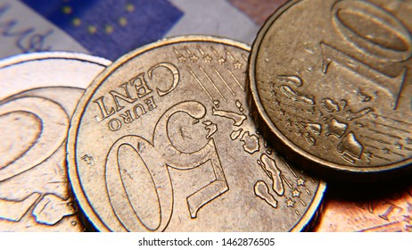 """Euro currency (coins) on a paper bill of five euros. Extreme close up, Macro. Coins texture. 50 euro coins and the words """"EURO CENT"""". European economics and finance, concept."""