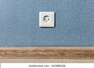 Euro electric outlet type C, electrical point of power in house, on the blue wall background.