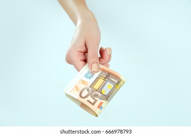 Euro money in the hands of a girl on a gray background