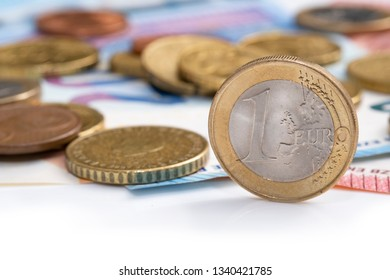 Euro money, image shows close-up of one euro coin with other coins and banknotes in background