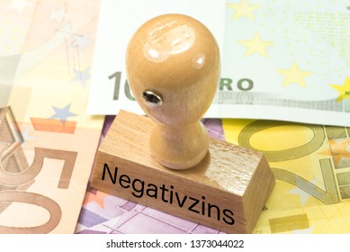 Euro money, a stamp and a German translation for a negative interest rate