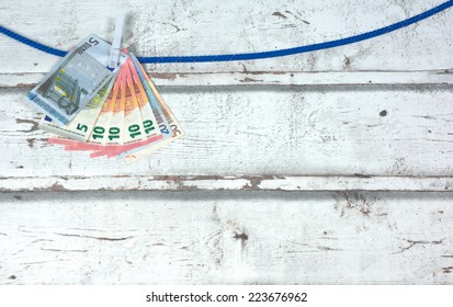 euro notes hanging as laundry on a line against a wooden background. The in 2014 introduced new banknote of ten (10) euro is included.