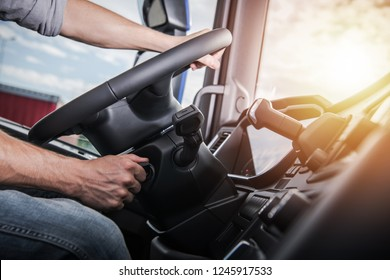 Euro Truck Driving. Modern Semi Truck Cabin Interior. Caucasian Trucker Placing Hand on a Steering Wheel.