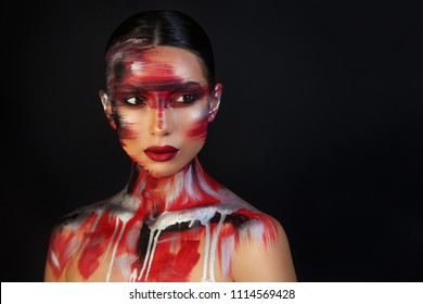the Euro-Asian woman looks away on a black background with bright red lips, unusual make-up with red, silver threads