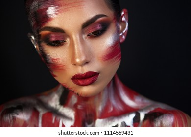 the Euro-Asian woman looks down, the red lips on a black background are well underline the image, a metallic red makeup.