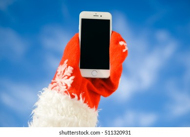 Europe - 03 November 2016: Santa claus with Apple Iphone 6 or 7 mobile phone ready for Christmas time, with blank black screen on sunny blue sky outdoors background