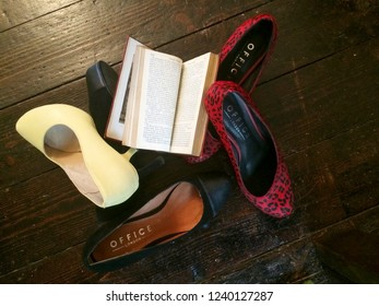 Europe Bedfordshire Bedford November 2018. Red and yellow high heeled ladies shoes on dark brown wooden floor. Open book on shoes. Still life concept. Fashion items.