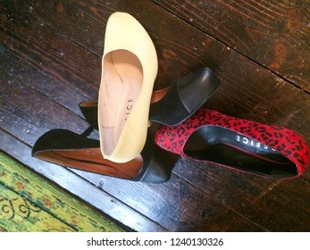 Europe Bedfordshire Bedford November 2018. Red and yellow high heeled ladies shoes on dark brown wooden floor. Still life concept. Fashion items. Vintage footwear.