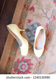 Europe Bedfordshire Bedford November 2018. Yellow high heeled ladies shoes on patterned floral carpet. Fashion items. Still life concept.