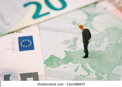 Europe, Brexit or Britain economy or financial concept, miniature figure businessman country leader standing on European map on Euro banknote looking at UK, England map.