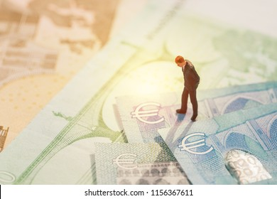 Europe economy, financial, investment or currency exchange concept, miniature businessman figurine standing and looking at Euro sign on pile of banknotes.