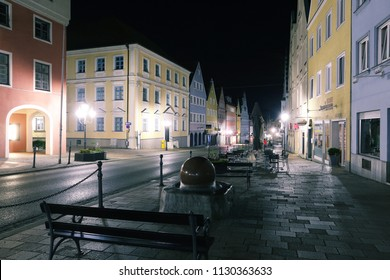 Europe, Germany, Bavaria, Swabia (Schwaben),  Donauwörth - June 06, 2018: romantic road of Germany, central street of old small town, bench near rotating stone ball in water, townscape night scene