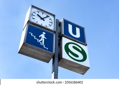 Europe, Germany: German traffic sign with time clock and symbols for subway metro station (U-Bahn), city train (S-Bahn) - concept public transport, traffic, tram, railway, transportation