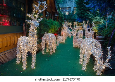 Europe is getting ready for Christmas. Beautiful colorful street of Andorra la Vella city decorated by rows of illuminated deers of Santa Claus. Christmas holiday and festive spirit concepts.