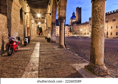 Europe Italy Mantua ancient roman town and Ducale residence at sunset central square covered with cobblestone surrounded by churches, towers, palace, colonnade, cafes all illuminated