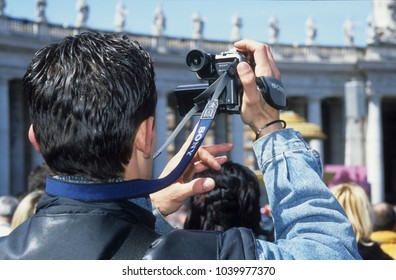 Europe Italy Rome 2001. Caucasian man in Vatican Square holding up video camera to view religious event. Easter time. Man back to camera.