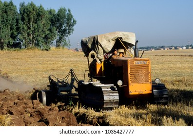 Europe Italy Rome 2004. Arable land outside city. Drought conditions of soil. Farmer ploughing the field with crawler tractor.