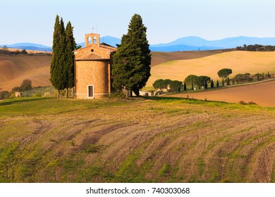 Europe, Italy,Tuscany. San Quirico d'Orcia. The Chapel of Our Lady of Vitaleta. Old small chapel and cypress trees.
