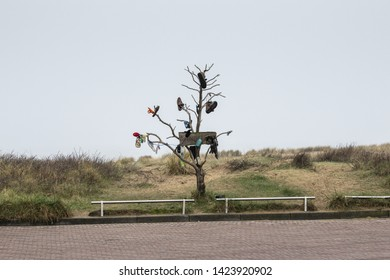 Europe, Netherlands, 2018-04, A tree used as a lost property point, mainly shoes, on the Noordwijk strand, one of South Holland's main tourist destinations for German and Dutch holiday makers.