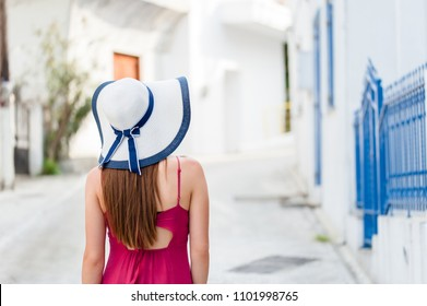 Europe summer travel destination Greece tourist woman on vacation, walking on the streets of old and beautiful villages in Greece, with sun hat and summer dress.