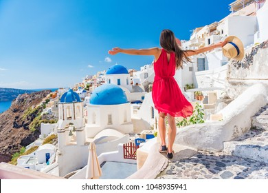 Photo of Europe travel vacation fun summer woman dancing in freedom with arms up happy in Oia, Santorini, Greece island. Carefree girl tourist in European destination wearing red fashion dress.