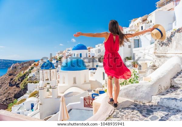 Europa Reisen Urlaub Spaß Sommer Frau Tanzen in Freiheit mit Waffen glücklich in Oia, Santorini, Griechenland Insel. Pflegefreie Girl-Touristen in Europa Ziel mit rotem Modekleid.